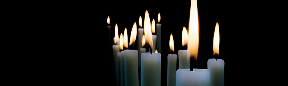 Kerzen in der Dunkelheit stehen für Beerdigung und Abschied